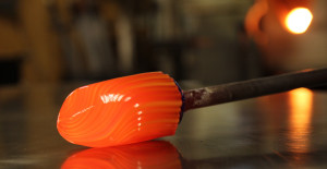 Zac Gorell rolling hot glass on metal table top